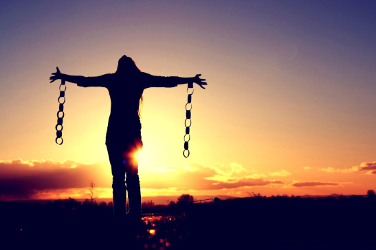 Woman with sunset or sunrise in the background with arms out and broken chains hanging from her wrists